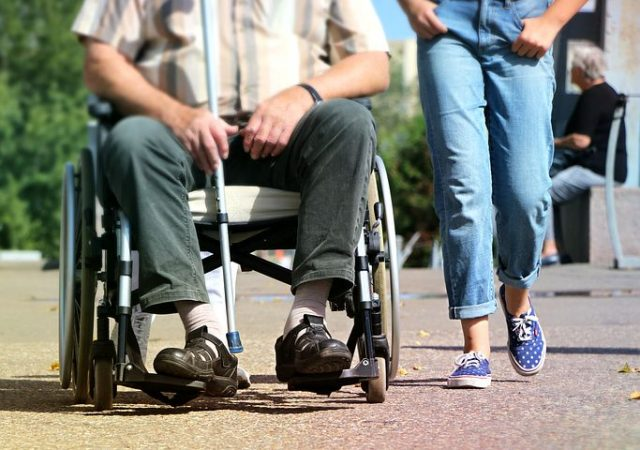 disability support worker walking next to a man on a wheelchair